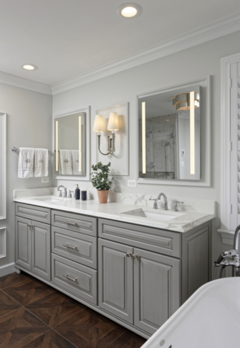 a traditional master bathroom with lit mirrors and chrome wall sconces