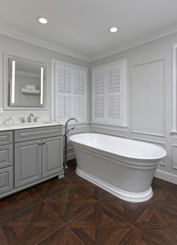 a traditional master bathroom with freestanding tub