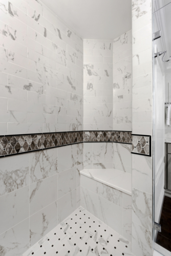 a traditional master bathroom shower with chrome fixtures and mosaic tile detail