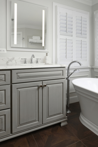 A traditional master bathroom with gray cabinets and a free standing tub